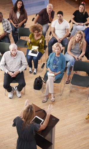 Overhead View Of Group Attending Neighborhood Meeting In Community Center